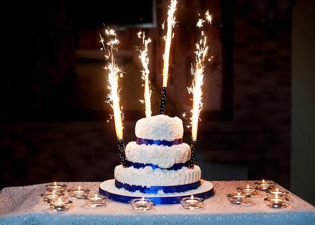 Hermoso pastel de bodas de tres capas con fuegos artificiales