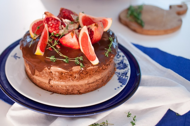Hermoso pastel con crema y decoración de pomelo y granada