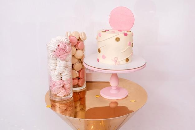 Hermoso pastel de cumpleaños con decoración rosa para el cumpleaños de un niño de un año. barra de caramelo con macarrones y malvaviscos