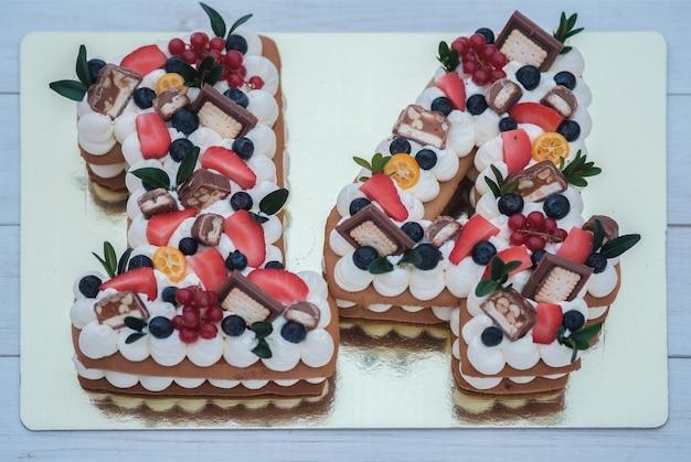 Hermoso pastel de cumpleaños en forma de número catorce en una vista superior de sustrato dorado