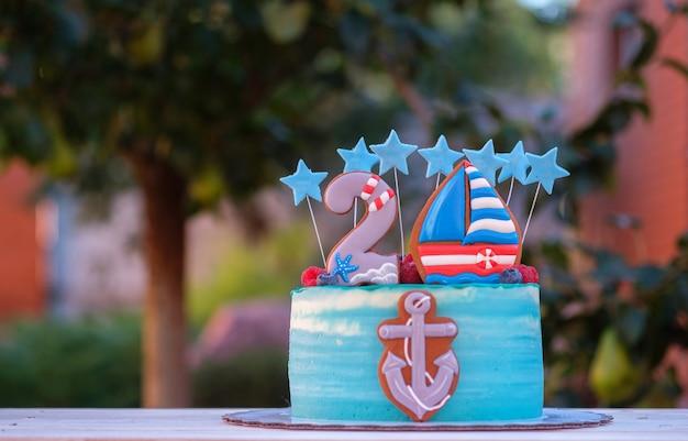 Hermoso pastel para el cumpleaños de un niño con el número dos y un ancla de barco en el jardín de verano
