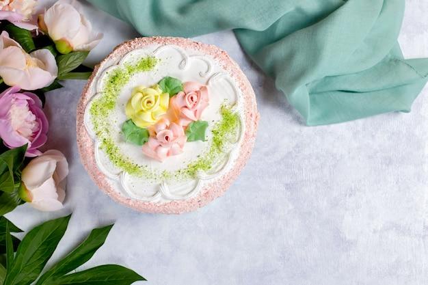 Hermoso pastel delicioso decorado con flores en colores pastel sobre mesa de madera con peonías, vista superior