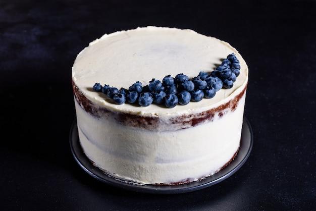 Hermoso pastel sabroso con crema blanca y bayas de arándano