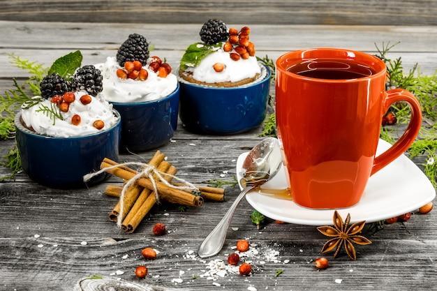 Hermoso pastelito de navidad con crema y bayas sobre fondo de madera conos de canela