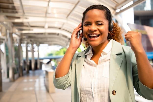 Hermoso personal del centro de llamadas hablando y brindando servicios a los clientes a través de auriculares y cable de micrófono en el paisaje urbano exterior.