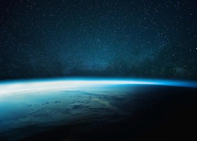 Hermoso planeta tierra azul con resplandor azul con vía láctea y estrellada. amanecer en el espacio