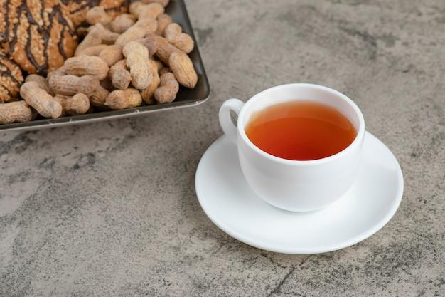 Un hermoso plato de galletas de avena con nueces y una taza de té caliente.