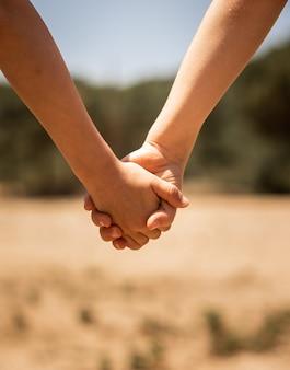 Hermoso primer plano de una pareja cogidos de la mano sobre un fondo borroso de un campo