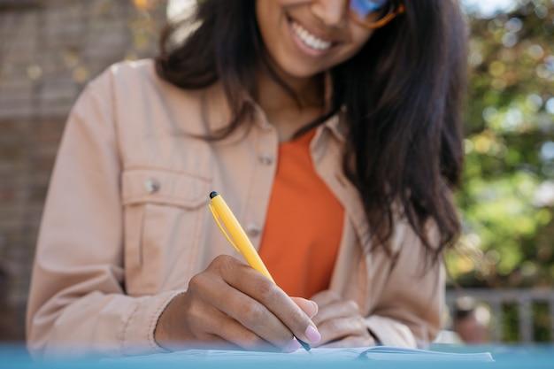 Hermoso proyecto de trabajo de mujer de negocios afroamericana, sosteniendo la pluma, tomando notas en el cuaderno, sentado en el lugar de trabajo