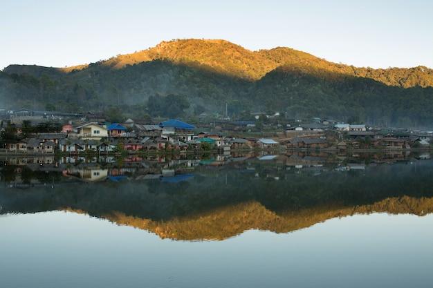 Hermoso pueblo de montaña alrededor del lago con reflejo en mae hong son, tailandia