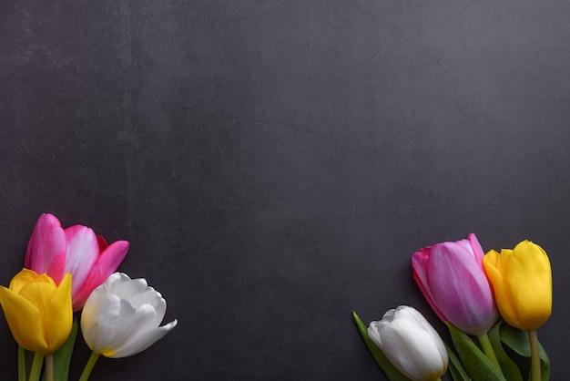 Un hermoso ramo brillante de tulipanes multicolores en primer plano contra una pared gris oscuro.