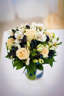 Hermoso ramo delicado con rosas coralinas y bayas azules