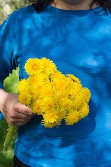 Hermoso ramo de dientes de león amarillos en forma de bola en la mano de la niña