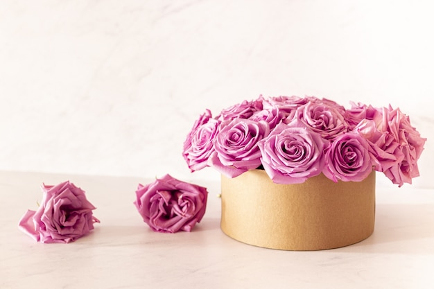 Hermoso ramo floral con rosas rosadas en una caja sobre un fondo rosa