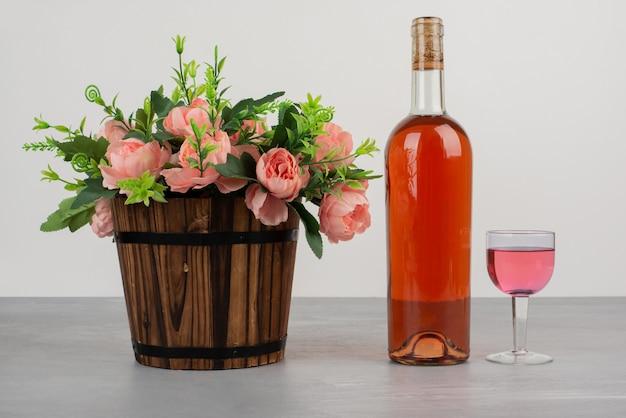 Hermoso ramo de flores y una botella de vino rosado en mesa gris