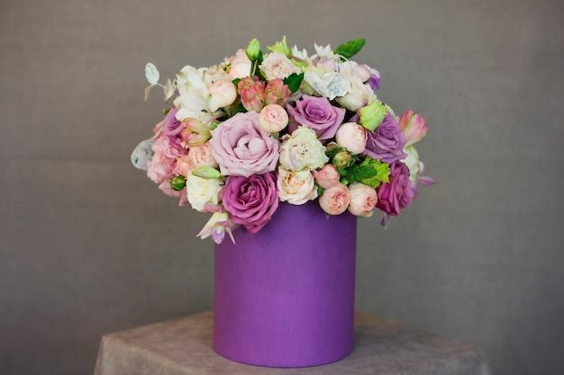 El hermoso ramo de flores en caja púrpura sobre fondo gris
