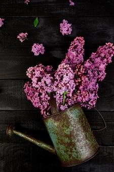 Hermoso ramo de flores de color lila en regadera de metal, maceta