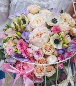Un hermoso ramo de flores de color pastel en un contenedor de jaula