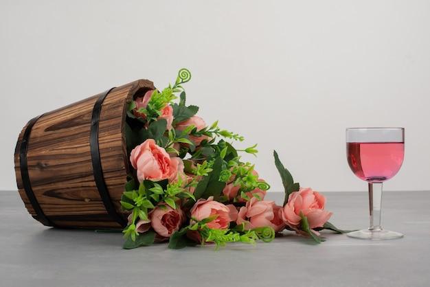 Hermoso ramo de flores y copa de vino rosado en mesa gris.