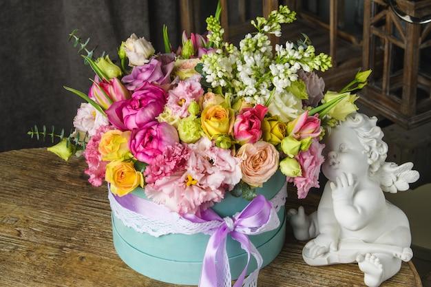 Hermoso ramo de flores y estatuillas de cupido
