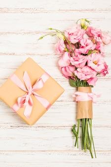 Hermoso ramo de flores frescas de eustoma rosa con caja actual en superficie de madera