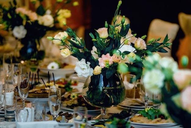 Hermoso ramo de flores en la mesa de la boda en un restaurante para las vacaciones y la cena de bodas
