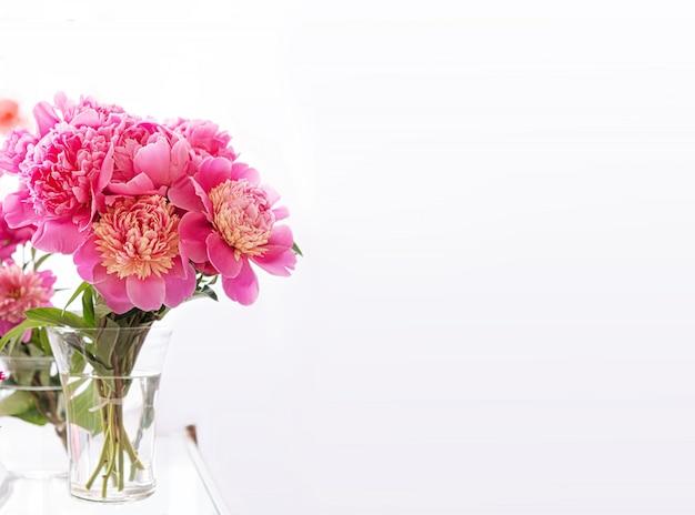 Hermoso ramo de flores de peonía fresca en un florero de vidrio transparente sobre un fondo blanco.
