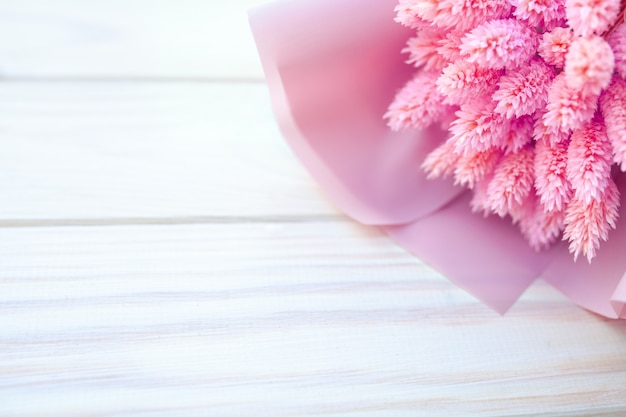 Hermoso ramo de flores rosadas secas sobre un fondo blanco de madera