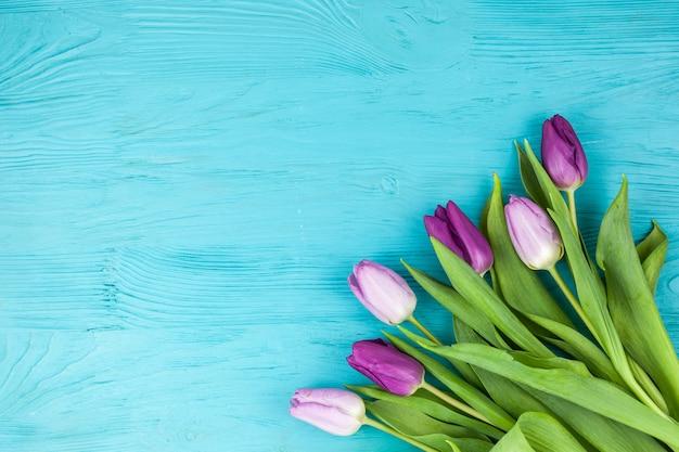 Hermoso ramo de flores de tulipán en superficie turquesa