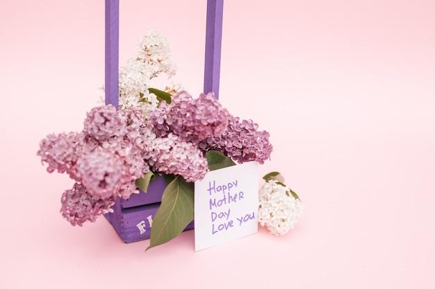 Hermoso ramo de lila púrpura y tarjeta sobre fondo de papel púrpura