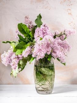 Hermoso ramo de lilas en florero de cristal sobre fondo con textura ligera