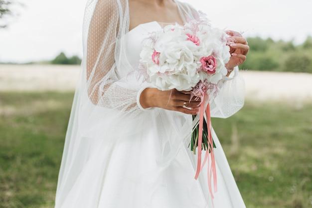 Hermoso ramo de novia hecho de narcisos blancos con middles rosados en las manos de la novia al aire libre
