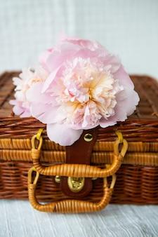 Un hermoso ramo de peonías rosas en un jarrón se alza sobre una maleta de madera. hermosa composición