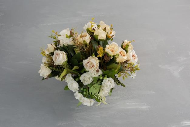 Hermoso ramo de rosas blancas sobre mesa gris.