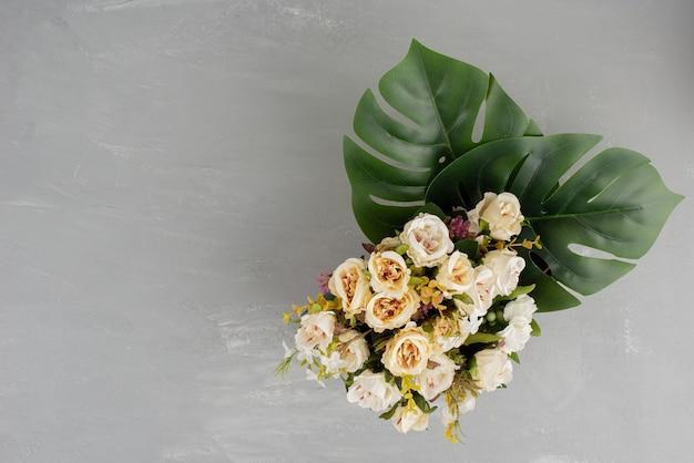 Hermoso ramo de rosas blancas sobre superficie gris.