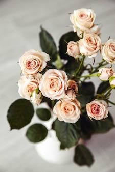 Hermoso ramo de rosas durazno en florero vintage sobre un fondo negro
