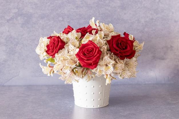 Hermoso ramo de rosas rojas y flores de lirio en una caja