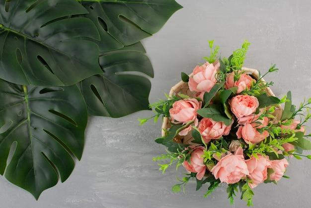 Hermoso ramo de rosas rosadas en mesa gris.