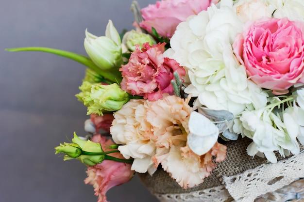 El hermoso ramo rústico de flores en cesta de mimbre.