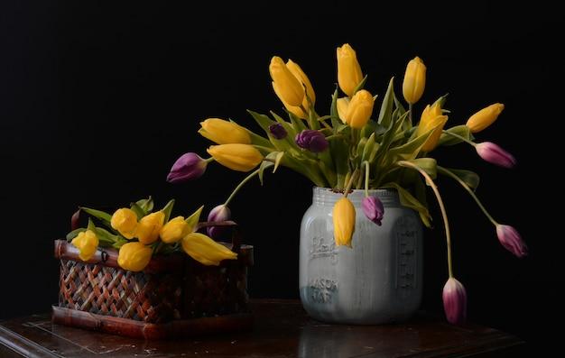 Hermoso ramo de tulipanes amarillos y morados en un jarrón gris sobre la mesa marrón
