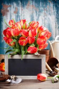 Hermoso ramo de tulipanes, huevos de pascua y herramientas de jardín en mesa de madera