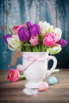 Hermoso ramo de tulipanes y huevos de pascua en mesa de madera