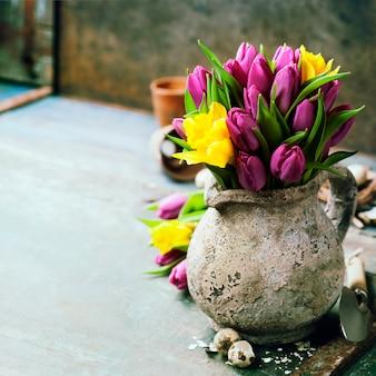 Hermoso ramo de tulipanes de primavera, huevos de pascua y herramientas de jardín