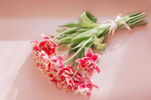 Hermoso ramo de tulipanes rosas para el día de la madre en una mesa rosa, vista superior