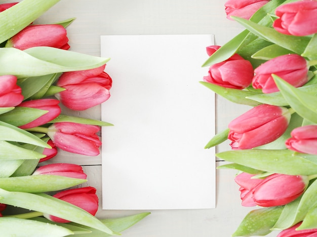 Hermoso ramo de tulipanes con tarjeta de felicitación blanca en blanco