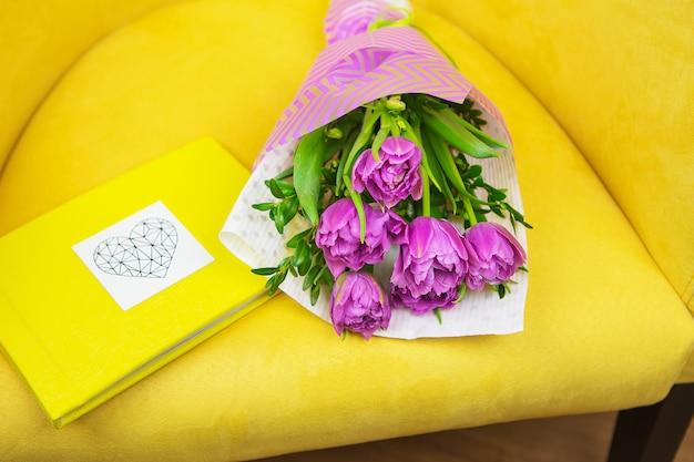Hermoso ramo violeta de tulipanes en un taburete amarillo y libro amarillo