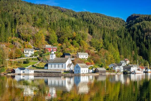 Hermoso reflejo de agua de la casa blanca de noruega en el fiordo, noruega