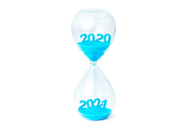 Hermoso reloj de arena que contiene arena azul que fluye hacia abajo para cambiar de 2020 a 2021