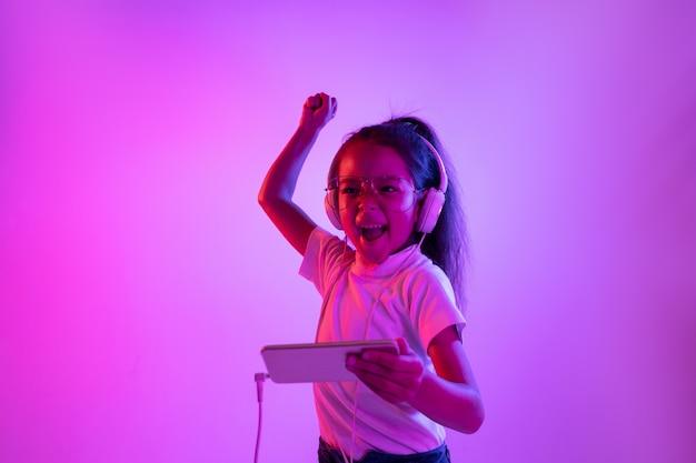 Hermoso retrato femenino aislado sobre fondo púrpura en luz de neón. chica emocional en anteojos. las emociones humanas, el concepto de expresión facial. bailar, escuchar música, jugar y ganar.