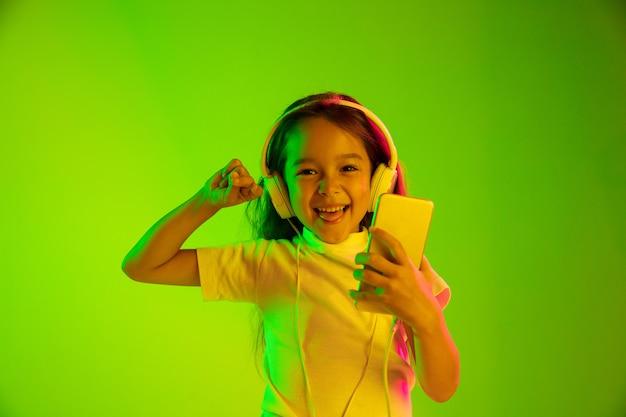 Hermoso retrato femenino de medio cuerpo aislado en la pared verde en luz de neón. chica joven emocional. las emociones humanas, el concepto de expresión facial. uso de teléfonos inteligentes para vlog, selfies, chats, juegos.
